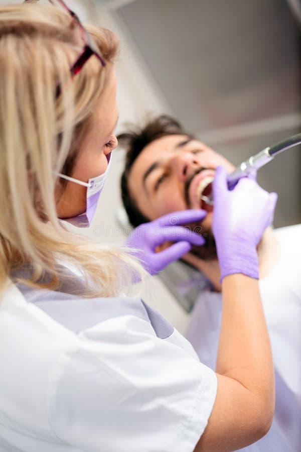 Vue courbe d'un beau jeune dentiste féminin polissant ou réparant la cavité dentaire sur les dents patientes masculines images stock
