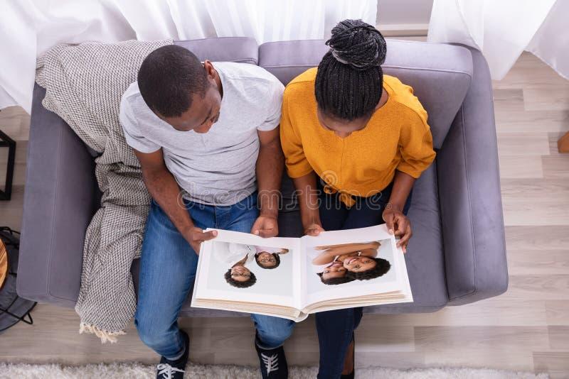 Vue courbe d'un couple regardant l'album photos images stock