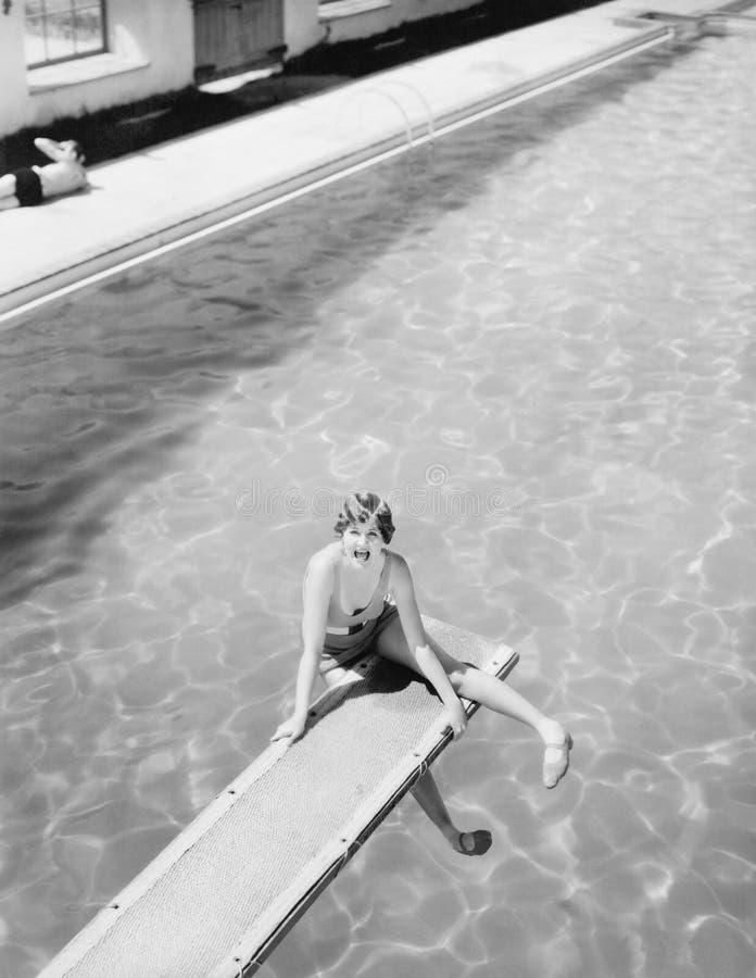 Vue courbe d'une femme s'asseyant sur un conseil de plongée et semblant crainte (toutes les personnes représentées ne sont pas pl photo libre de droits