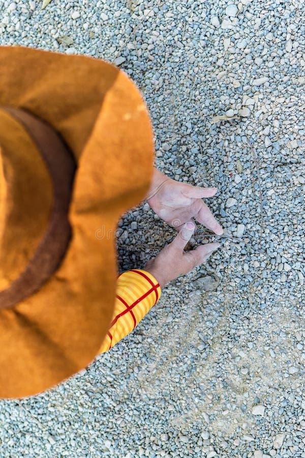 Vue courbe de bébé garçon de cowboy jouant au sol avec le sable et la saleté photographie stock libre de droits