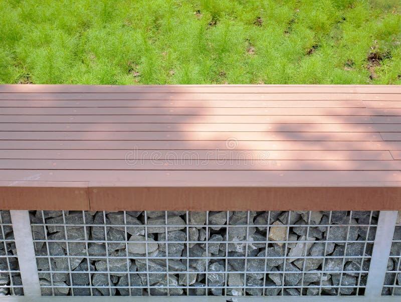 Vue courbe de banc en bois de planche avec des roches dessous images stock