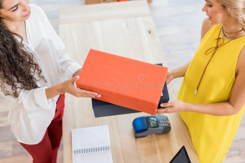 vue courbe de caissier donnant des boîtes à chaussures image libre de droits