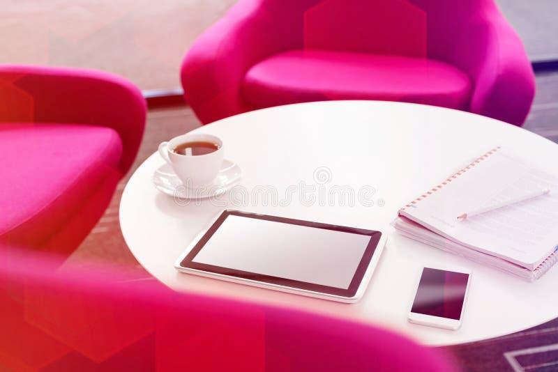 Vue courbe de comprim? num?rique avec la tasse de caf? et le smartphone sur la table par des chaises au bureau photos libres de droits