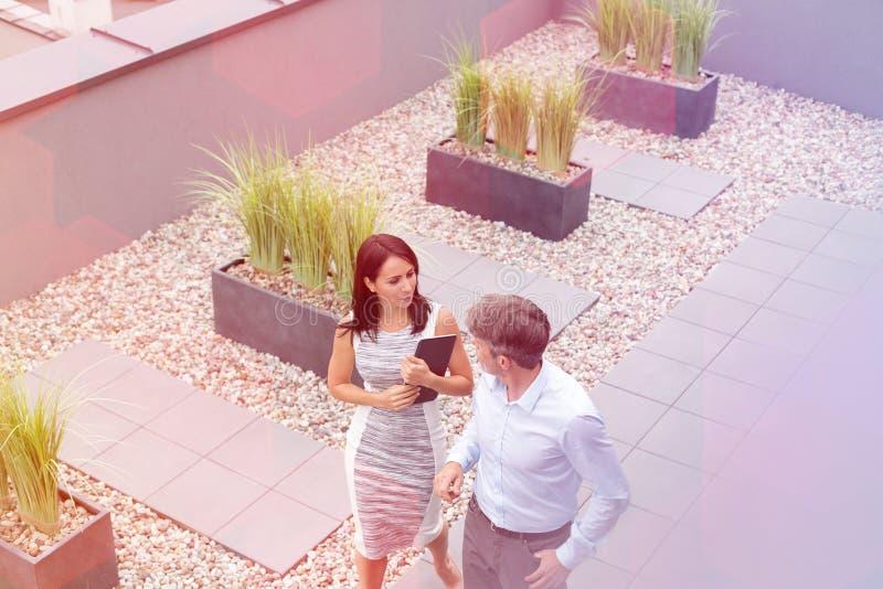 Vue courbe de femme d'affaires communiquant avec le coll?gue ? la terrasse de bureau image stock
