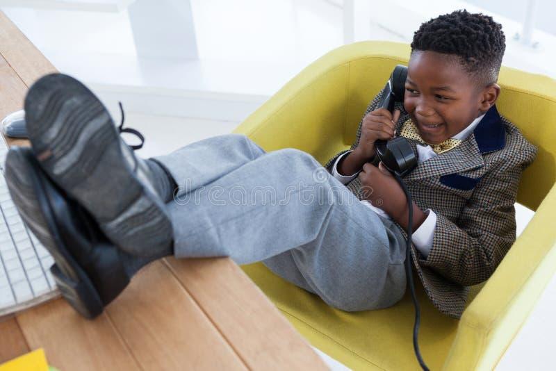 Vue courbe de garçon heureux imitant comme homme d'affaires parlant au téléphone de ligne terrestre photo stock