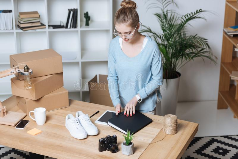 vue courbe de jeune entrepreneur se tenant sur le lieu de travail avec les boîtes et le carnet en carton photographie stock libre de droits
