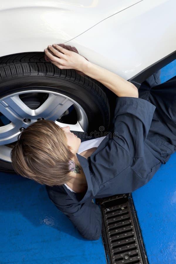 Vue courbe de jeune mécanicien se trouvant sur le plancher travaillant au pneu de voiture dans le garage photos libres de droits