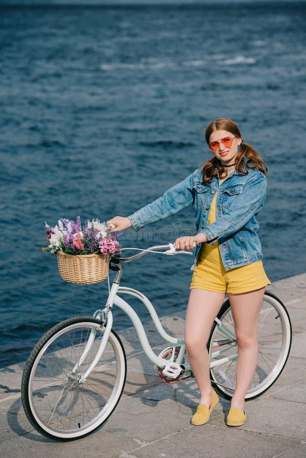 vue courbe de la fille dans des lunettes de soleil souriant à la caméra tout en se tenant avec la bicyclette image stock
