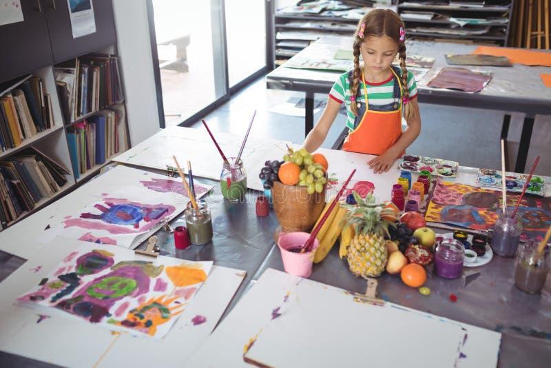 Vue courbe de la peinture concentrée de fille au bureau photos libres de droits