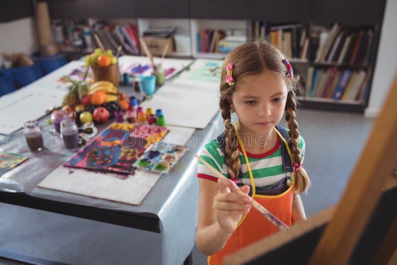 Vue courbe de la peinture de fille sur la toile photographie stock libre de droits