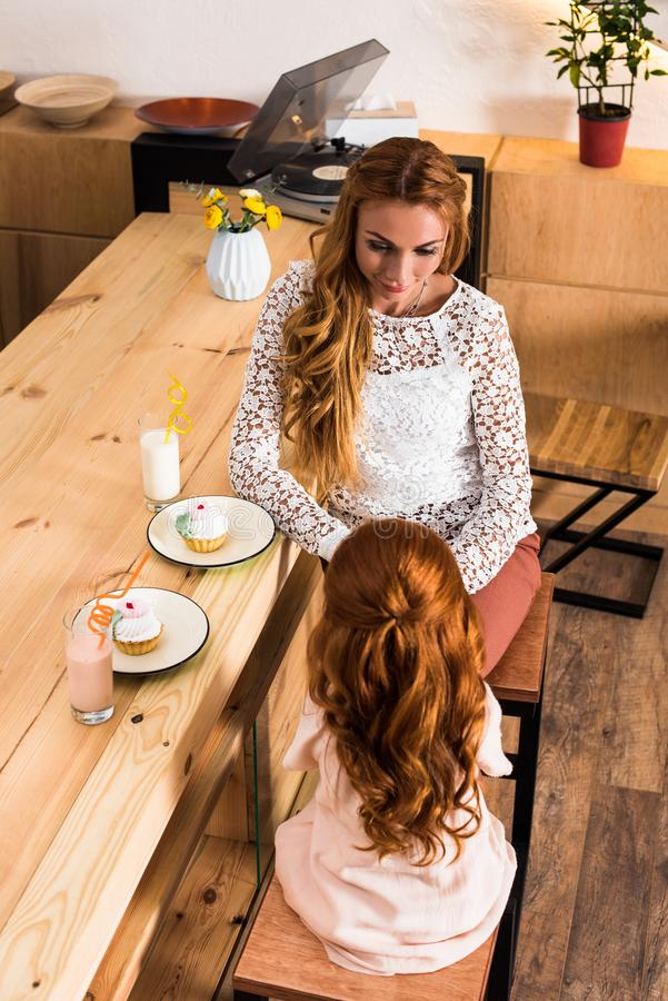 vue courbe de mère heureuse et de fille mangeant des petits gâteaux et buvant des milkshakes photographie stock libre de droits