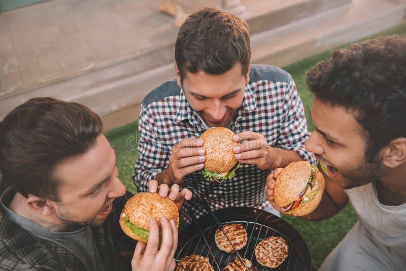Vue courbe de trois jeunes hommes mangeant les hamburgers frais image libre de droits
