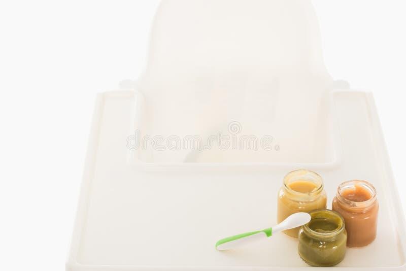 vue courbe de trois pots avec la purée et la cuillère d'enfant sur le highchair photos libres de droits