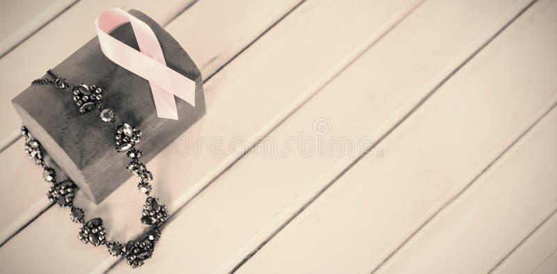 Vue courbe des bijoux avec la boîte rouge et le ruban rose de conscience de cancer du sein photos stock