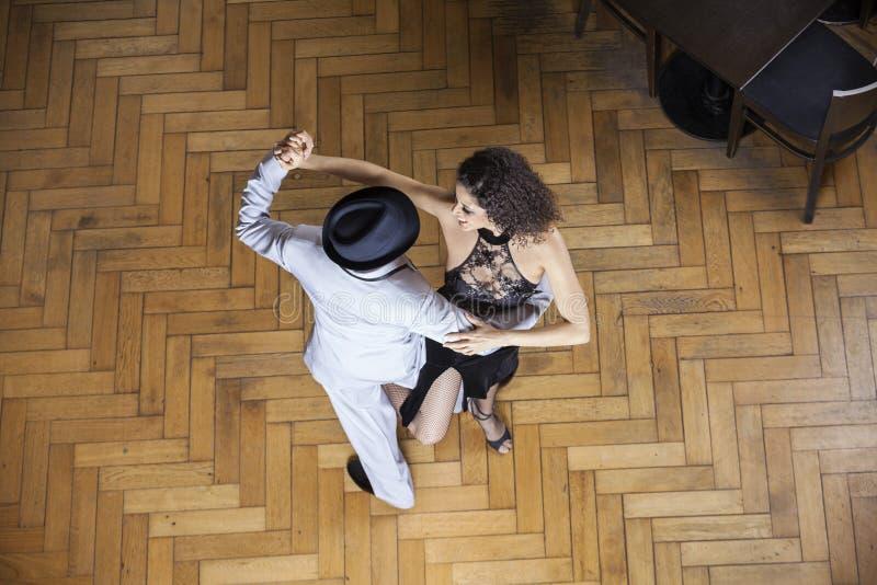 Vue courbe des danseurs exécutant sur le plancher en bois images libres de droits