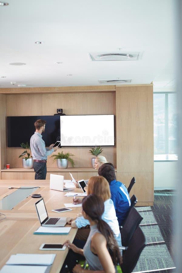 Vue courbe des gens d'affaires à la table de conférence au cours de la réunion photo libre de droits