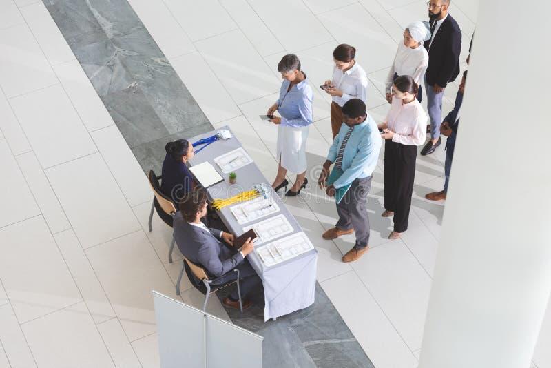 Vue courbe des hommes d'affaires signant à la table d'enregistrement de conférence photos stock