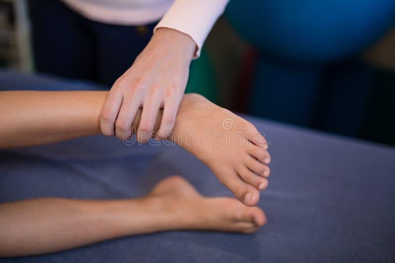 Vue courbe des pieds de examen de thérapeute féminin avec le garçon se trouvant sur le lit images stock