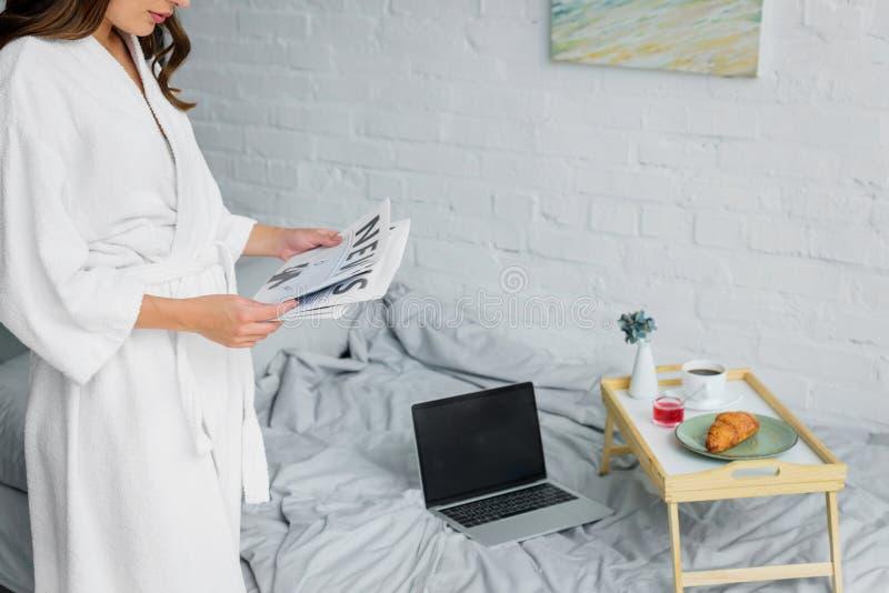 vue cultivée de femme en journal blanc de lecture de peignoir dans la chambre à coucher avec l'ordinateur portable et le petit dé image libre de droits