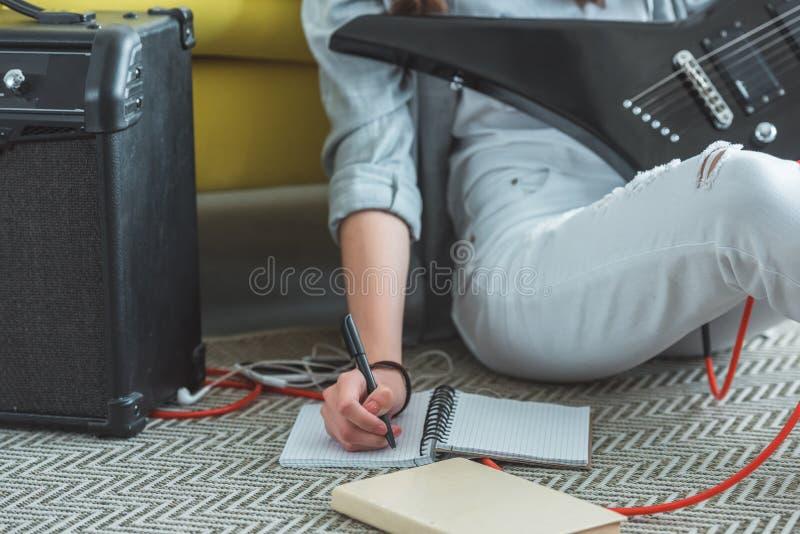vue cultivée de fille avec la chanson d'écriture de guitare électrique dans le cahier tout en se reposant photos stock