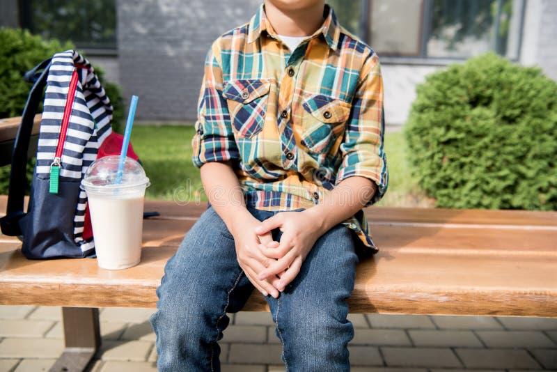 vue cultivée de garçon d'élève du cours préparatoire se reposant sur le banc avec le sac à dos photographie stock libre de droits
