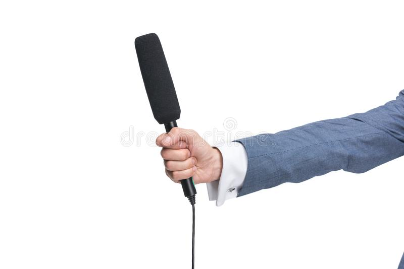 vue cultivée de la main masculine tenant le microphone pour l'entrevue, photo libre de droits
