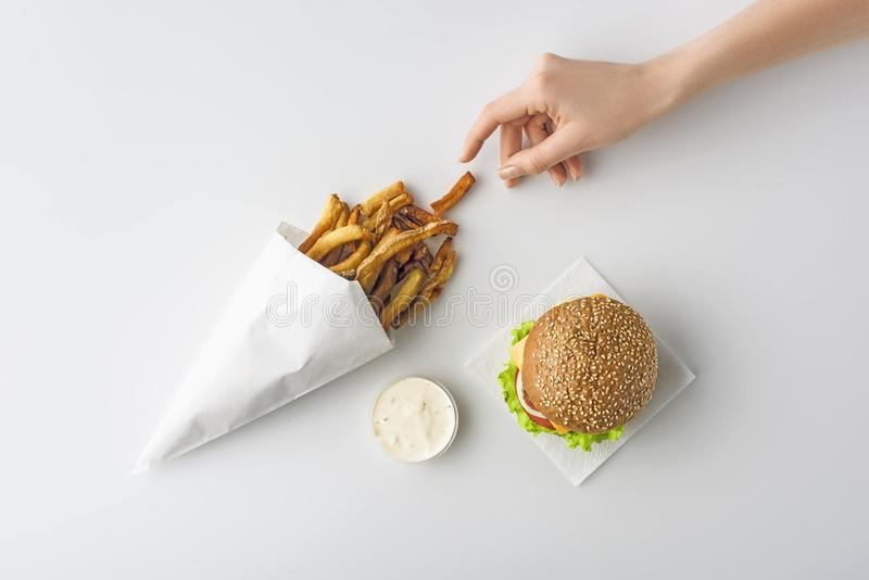 vue cultivée de main femelle avec les pommes frites, l'hamburger fait maison et la mayonnaise, images libres de droits