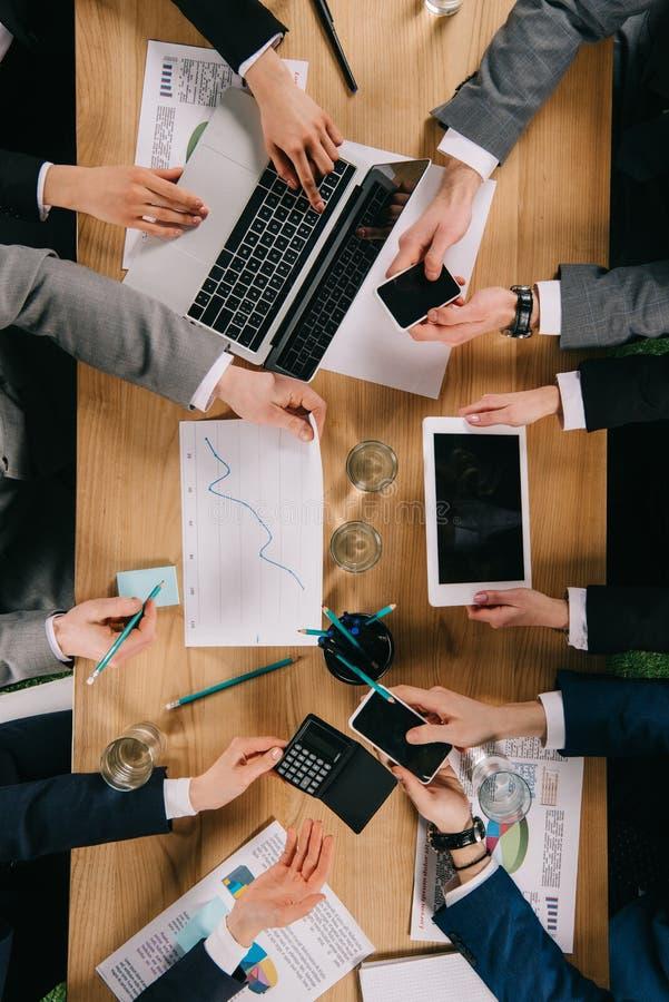 Vue cultivée des collègues d'affaires montrant les dispositifs numériques entre eux à la table photo libre de droits
