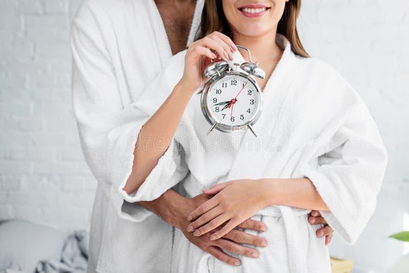 vue cultivée des couples dans des peignoirs blancs tenant le réveil et la position images stock