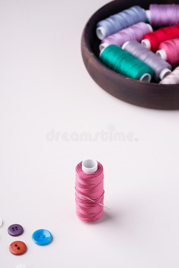 Vue d'angle de bobine rose de fil avec les boutons et l'aiguille photos libres de droits