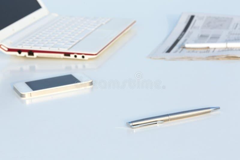 Vue d'angle de lieu de travail avec le stylo et le journal économique de téléphone d'ordinateur portable images libres de droits