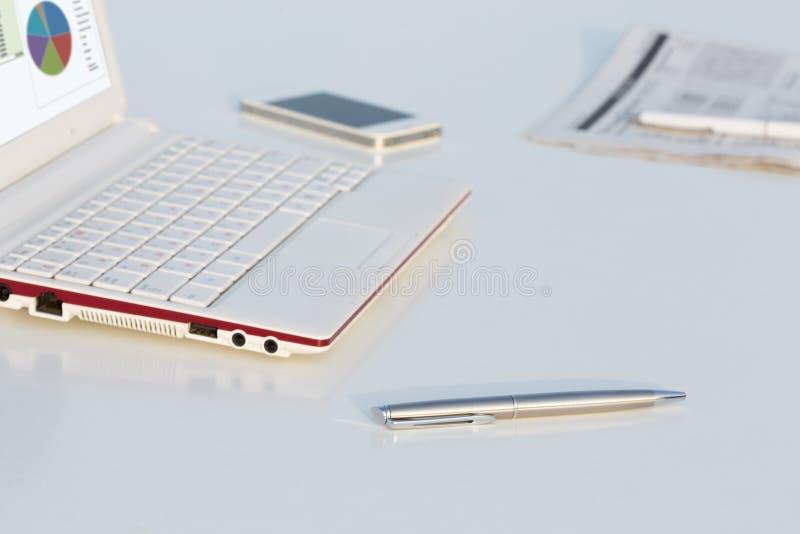 Vue d'angle de lieu de travail avec le stylo et le journal d'ordinateur portable photos libres de droits