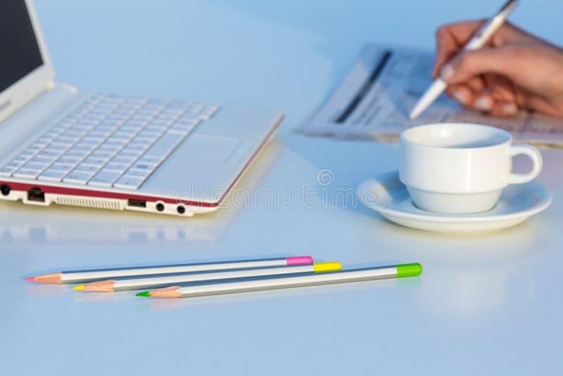 Vue d'angle de lieu de travail avec les crayons et le journal économique de couleur d'ordinateur portable images libres de droits