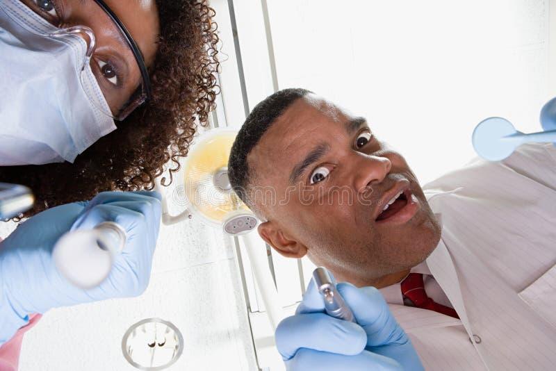 Vue d'angle faible de dentiste et d'infirmière dentaire photographie stock libre de droits