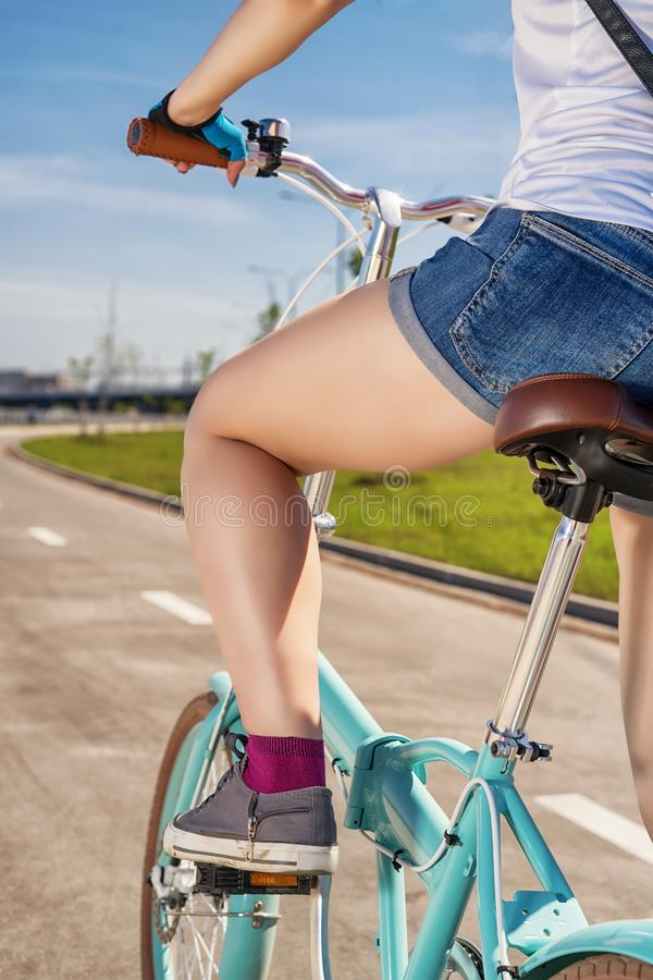 Vue d'angle faible de fille montant le vélo se pliant bleu photo stock