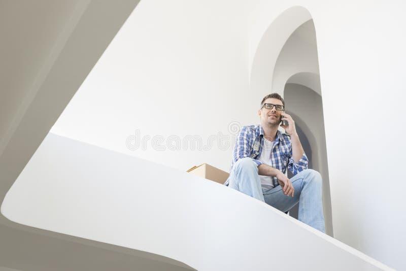 Vue d'angle faible de l'homme à l'aide du téléphone portable dans la nouvelle maison photo stock