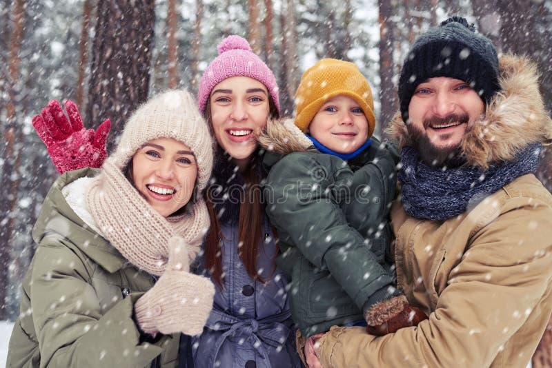 Vue d'angle faible de la famille heureuse de quatre personnes collant sur chaque ot photo stock