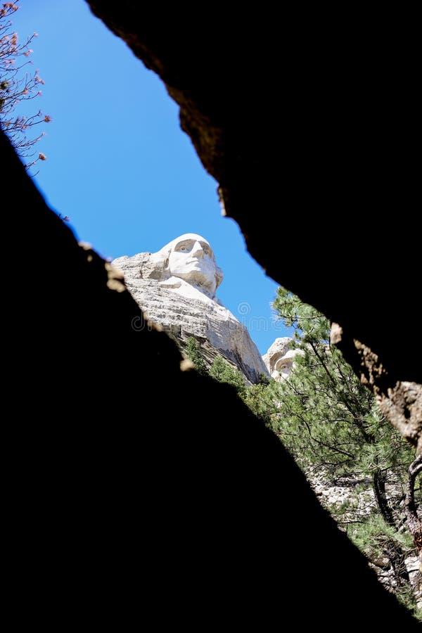 Vue d'angle faible de Mt Rushmore d'une crique dans une roche image stock