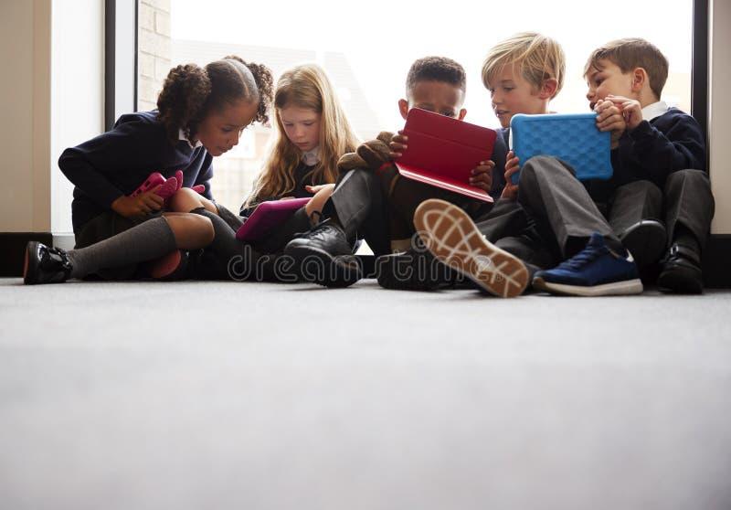 Vue d'angle faible des amis d'école primaire s'asseyant ensemble devant une fenêtre dans un couloir d'école regardant des tablett images libres de droits