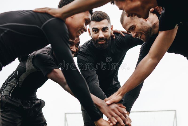 Vue d'angle faible des footballers parlant de la position de stratégie dans un petit groupe Footballeurs tenant leurs mains se te image libre de droits