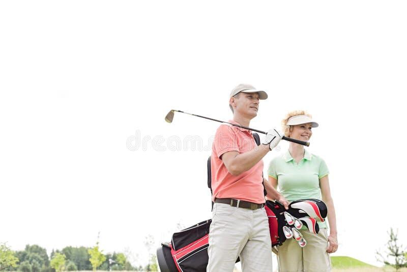 Vue d'angle faible des golfeurs de sourire se tenant contre le ciel clair photo stock