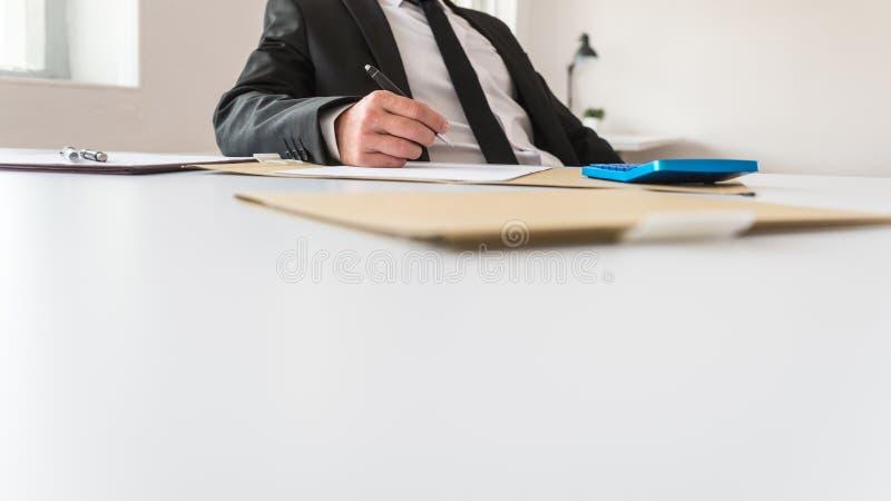 Vue d'angle faible du conseiller d'affaires ou du réviseur s'asseyant à son fonctionnement de bureau photo libre de droits