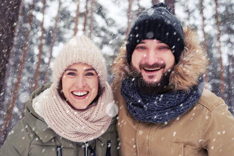 Vue d'angle faible du sourire et d'embrasser des couples sous le snowfal photographie stock libre de droits