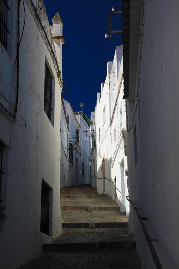 Vue d'angle faible sur l'allée vide étroite avec des façades des maisons blanches et des étapes différant en haut du ciel bleu-fo photo libre de droits