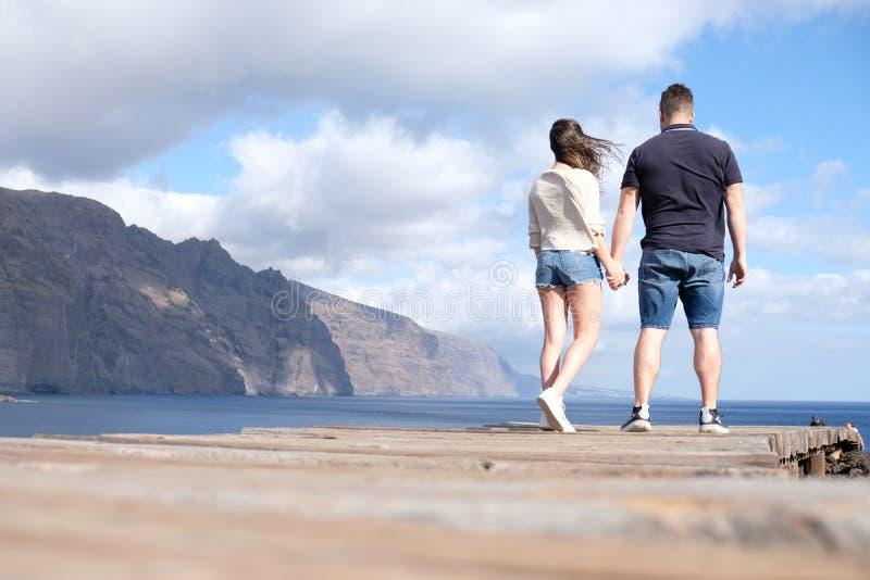 Vue d'angle faible d'un jeune couple tenant des mains avec les falaises, le ciel nuageux et la mer à l'arrière-plan photos libres de droits