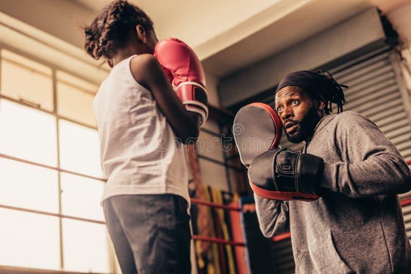 Vue d'angle faible d'une formation de fille de boxe avec son entraîneur photo libre de droits