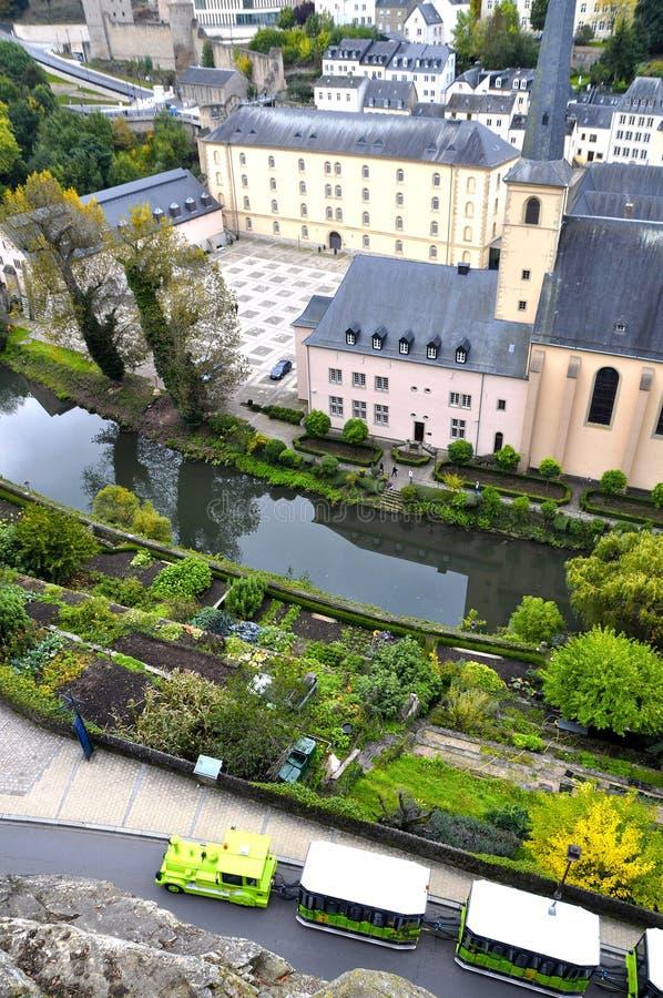Vue d'Arial du secteur de Grund de la ville du Luxembourg vu avec la rivière d'abbaye, d'Alzette de Neumuenster et le train touri images libres de droits