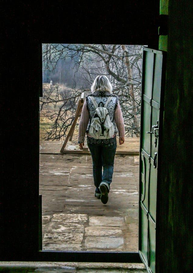 Vue d'arrière d'une femme partant Vue de porte d'une femme de touristes images libres de droits