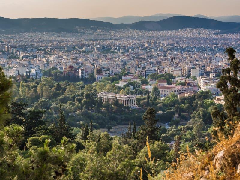 Vue d'Athènes de colline d'Acropole contre le coucher du soleil avec le temple de Hephaestus au centre photographie stock