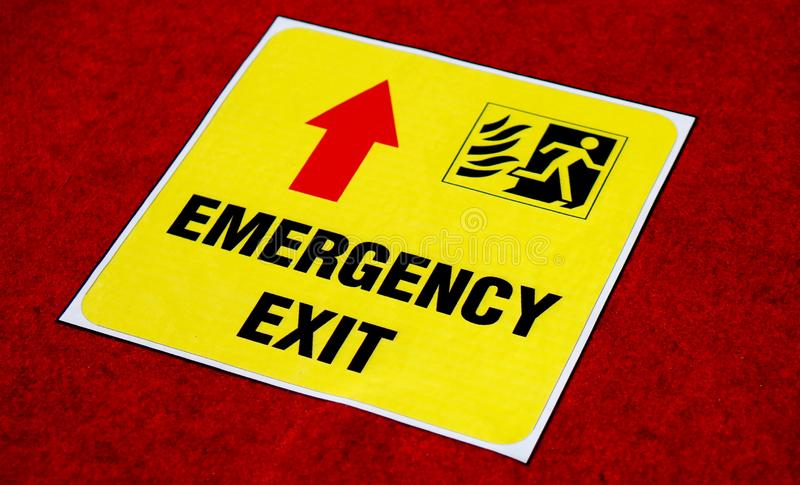 Vue d'autocollant de signe de manière de sortie de secours sur le plancher dans un lieu public images stock